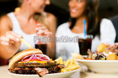 two women eating hamburger and drinking