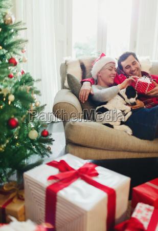 couple cuddling on sofa with dog