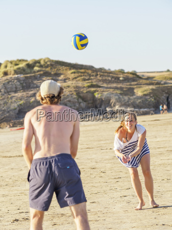 couple at the beach playing volleyball