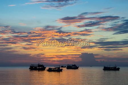 sun sets over scuba diving boats
