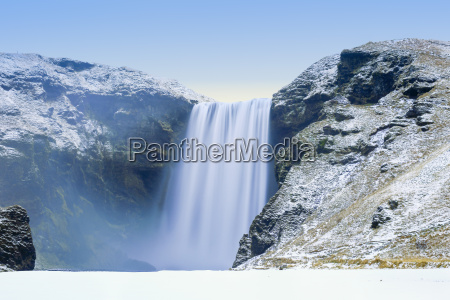skogafoss waterfall in snow iceland polar