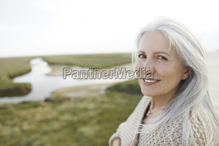 portrait smiling senior woman on beach