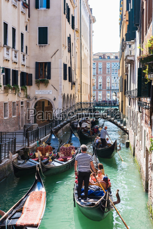 people on gondolas in canal rio