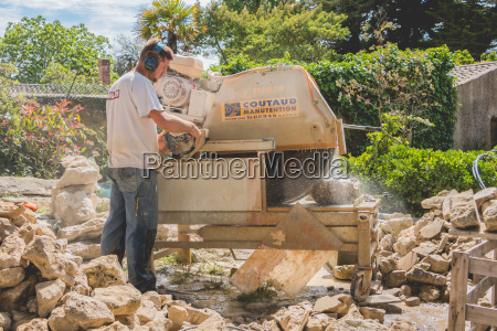 man cutting a stone with a