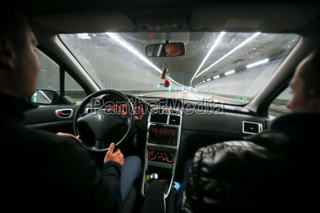 two men driving in tunnel